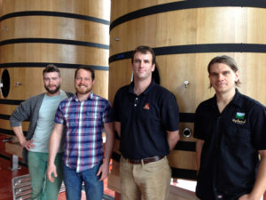 Caleb and his team in front of new foudres in the expanding sour brewery.